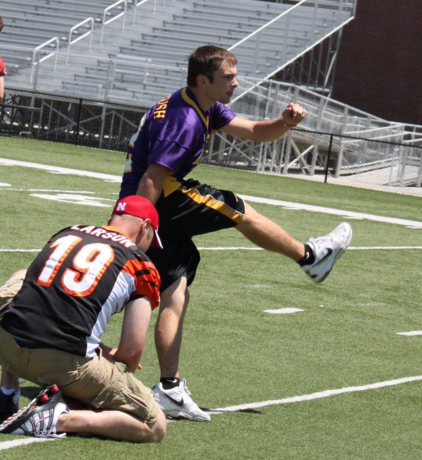 Lance English of Sumner kicks a football held by Kyle Larson at the 2011 Kicker's Kick-Off