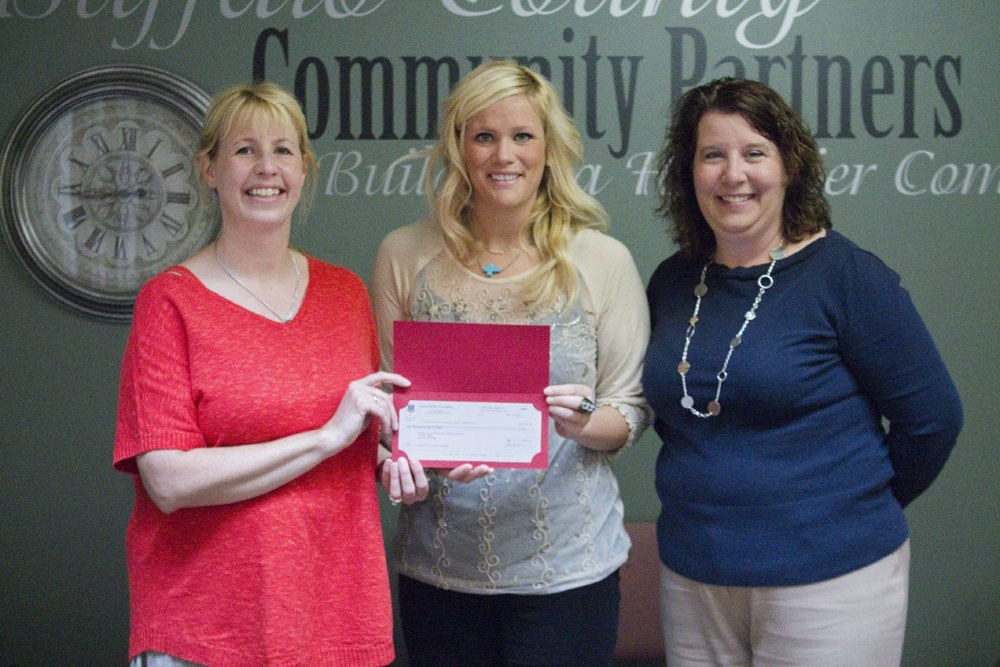 Kelli O'Brien of the Union Pacific Foundation presents a $10,000 check for Positive Pressure to Coalition Coordinator Tana Nelsen and Executive Director Denise Zwiener.
